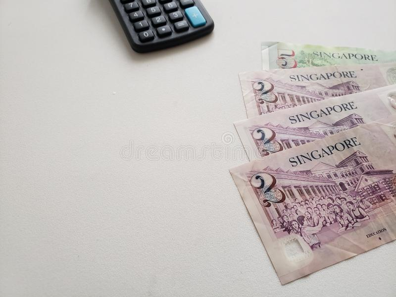 Singaporean bankbiljetten en calculator op witte achtergrond royalty-vrije stock afbeelding