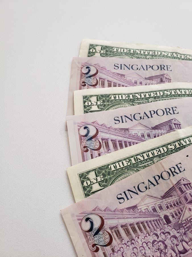 Singaporean bankbiljetten van twee dollars en Amerikaanse dollarrekeningen stock afbeeldingen
