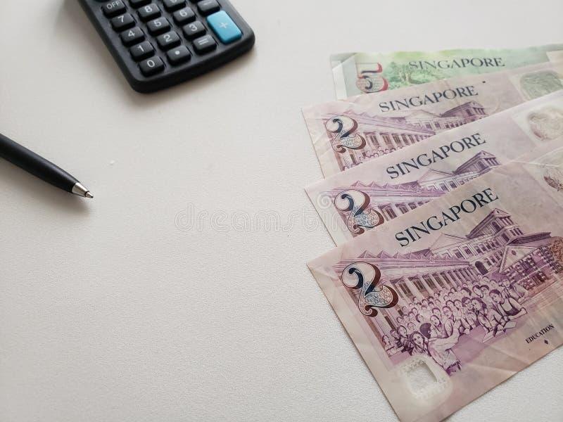 Singaporean bankbiljetten, zwarte pen en calculator op witte achtergrond royalty-vrije stock afbeeldingen