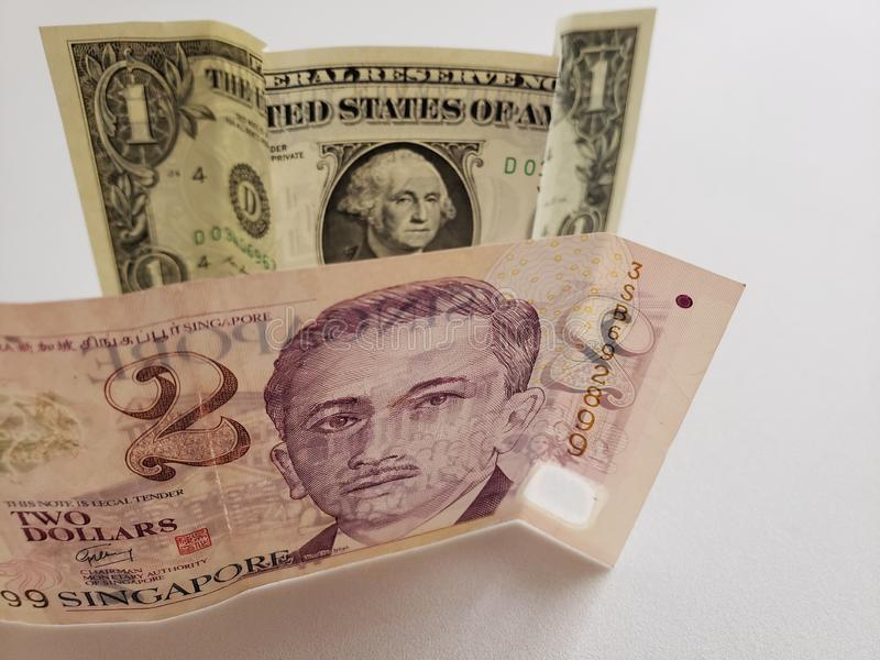 Singaporean banknote of two dollars and American one dollar bill royalty free stock image