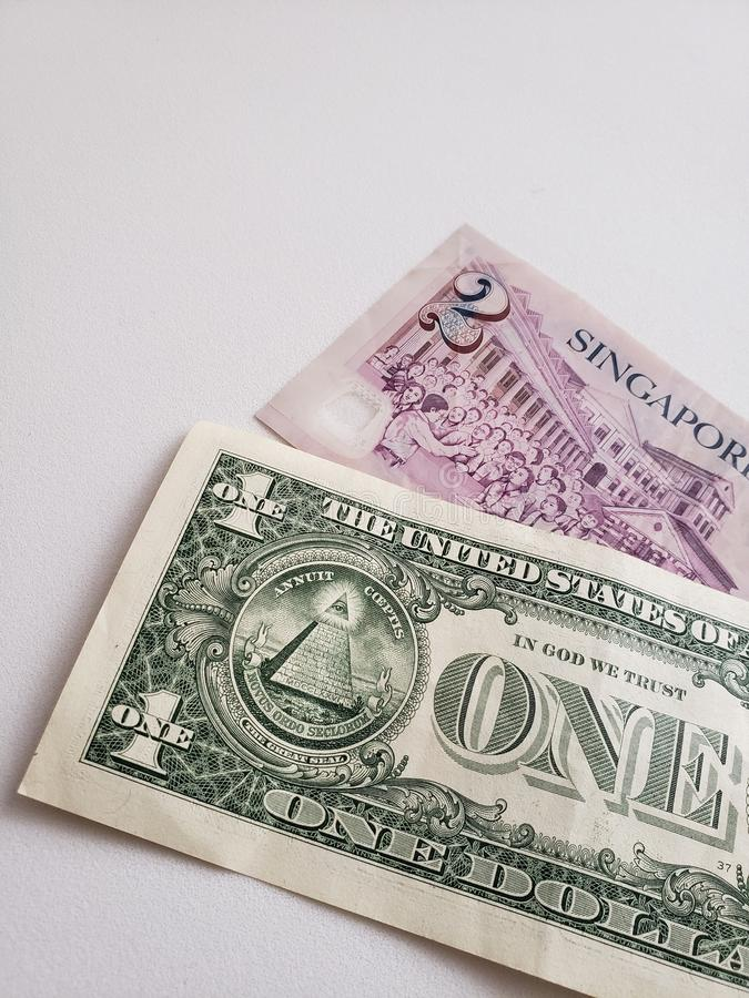 Singaporean banknote of two dollars and American one dollar bill stock photo