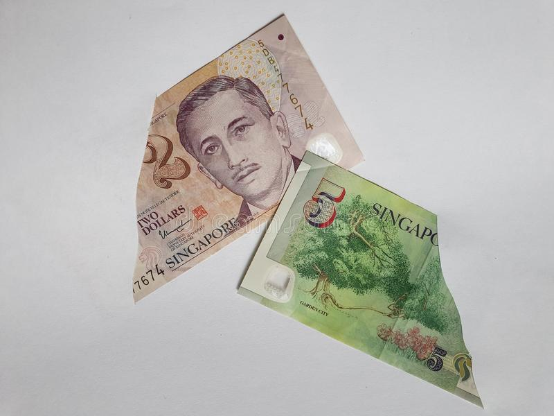 Singaporean banknotes of different denominations on the broken sheet of paper. Commerce, exchange, trade, trading, value, buy, sell, profit, price, rate, cash royalty free stock photo