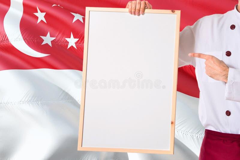 Singaporean Chef-kok die leeg whiteboardmenu op de vlagachtergrond van Singapore houden Kok die eenvormige richtende ruimte voor  stock afbeelding