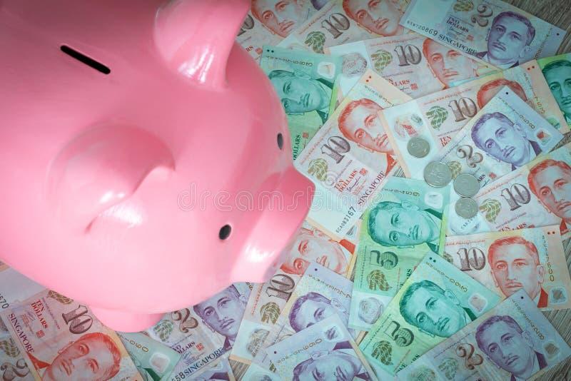Singaporean dollars en spaarvarken Het sparen en het deponeren geld royalty-vrije stock foto