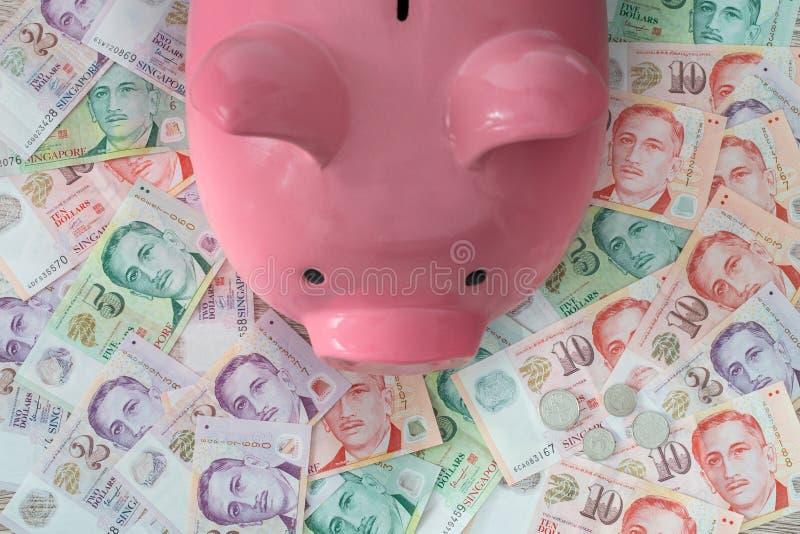 Singaporean dollars en spaarvarken Het sparen en het deponeren geld stock afbeelding
