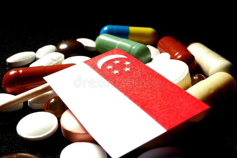 Singaporean vlag met partij van medische die pillen op zwarte bac wordt geïsoleerd stock afbeelding