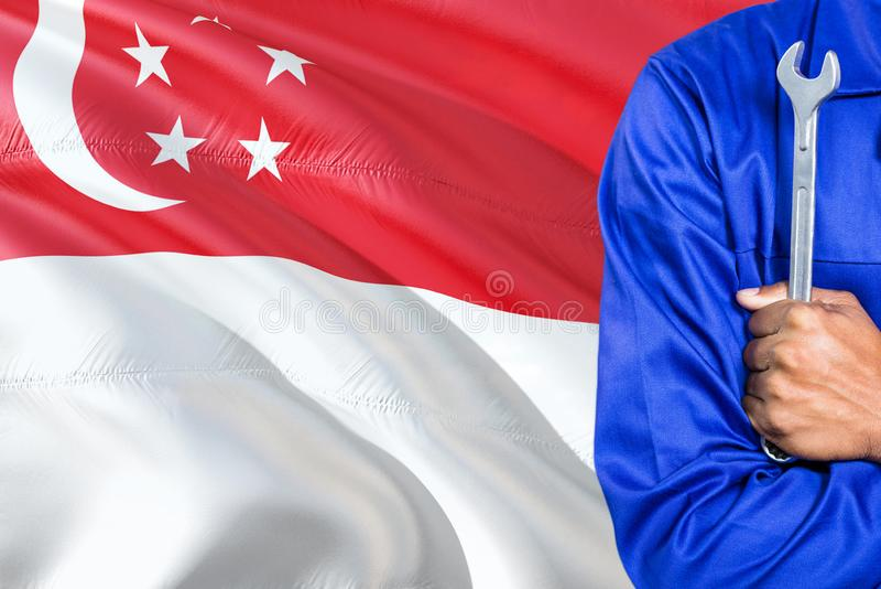 Singaporean Werktuigkundige in blauwe eenvormig houdt moersleutel tegen golvende de vlagachtergrond van Singapore Gekruiste wapen royalty-vrije stock fotografie