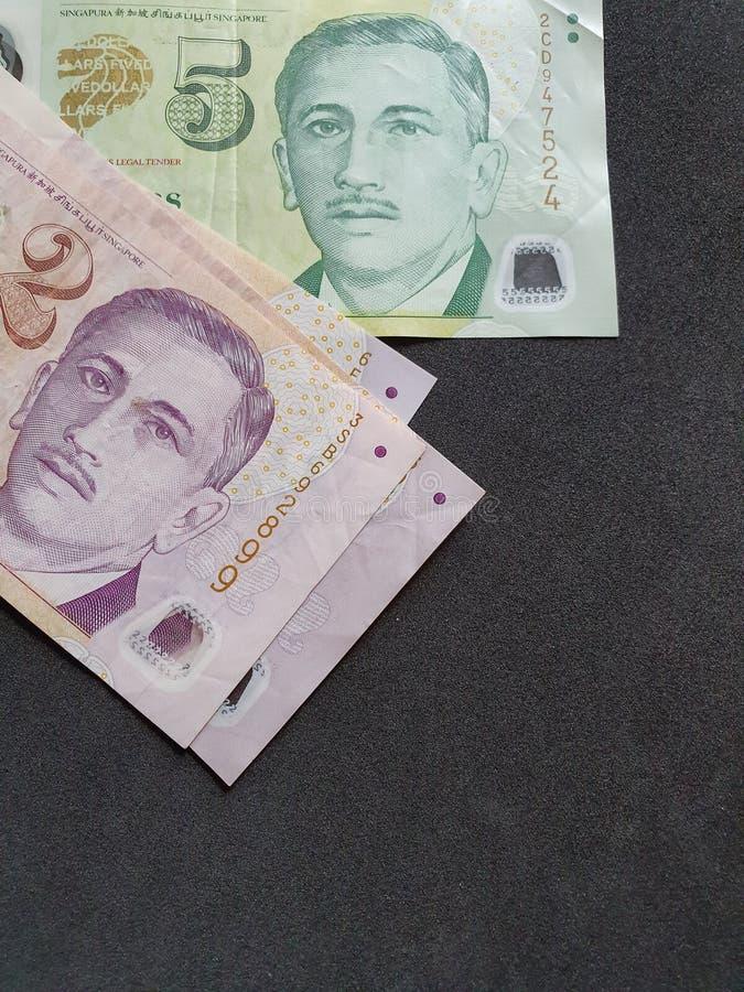 Singaporianska sedlar av olika valörer och svart bakgrund royaltyfri foto