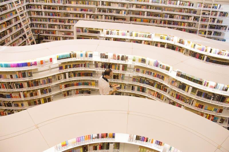 Singapur - 18. AUGUST 2016: library@orchard Bibliothek im Obstgarten Singapore Patreon beim Lesen eines Buches mit Wavy-Bookshelf lizenzfreies stockbild