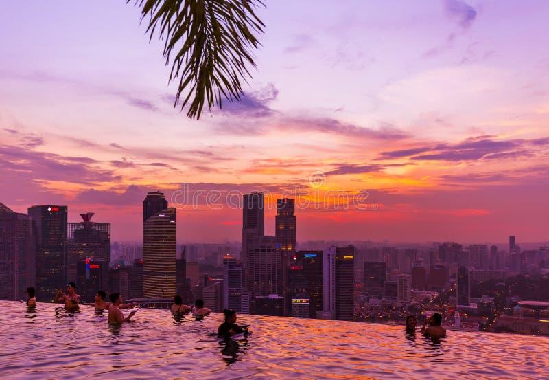 SINGAPUR - 14 DE ABRIL: Piscina en horizonte del tejado y de la ciudad de Singapur encendido fotografía de archivo libre de regalías
