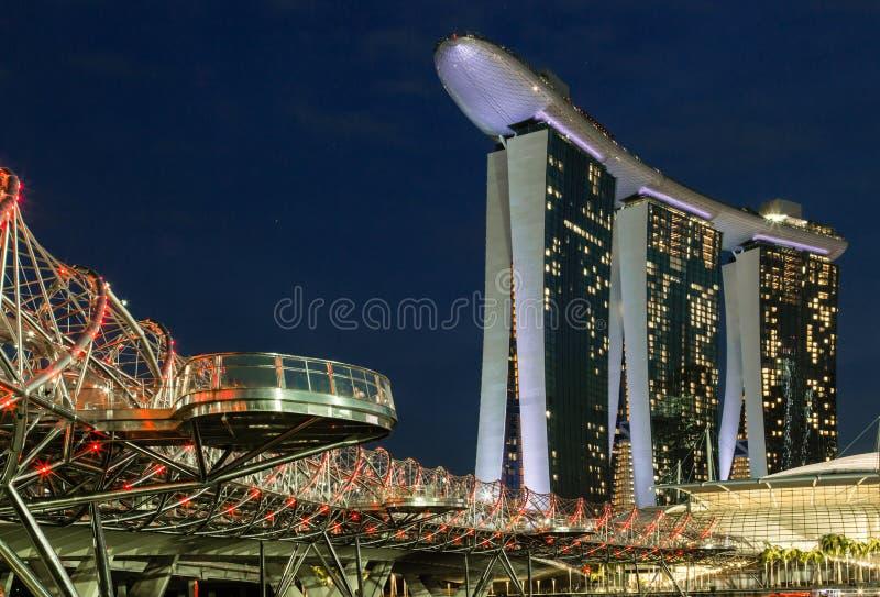 SINGAPUR 7 DE JUNIO DE 2017: Arenas de la bah?a del puerto deportivo de Singapur y puente de la h?lice en noche fotos de archivo libres de regalías