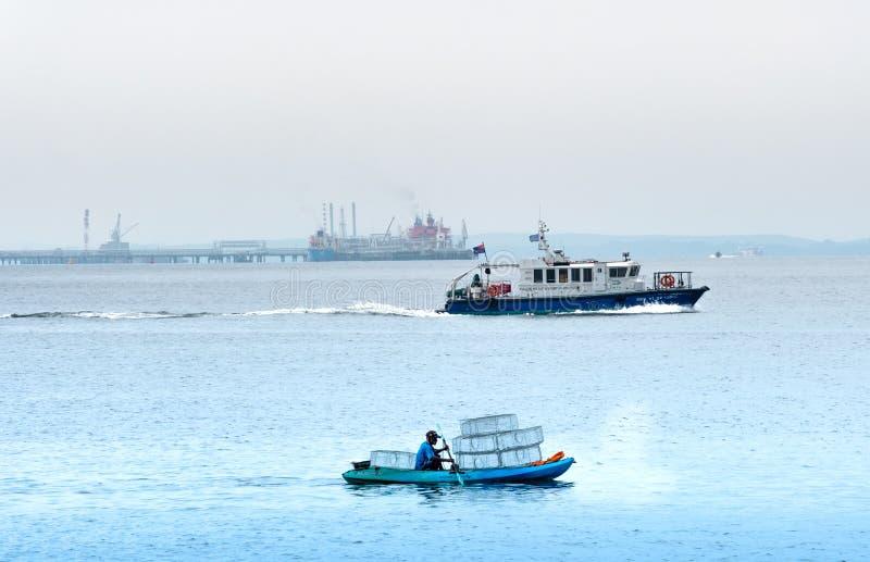 Singapur 29 DE JUNIO DE 2019: El pescador está pescando en el mar colocando jaulas fotos de archivo libres de regalías