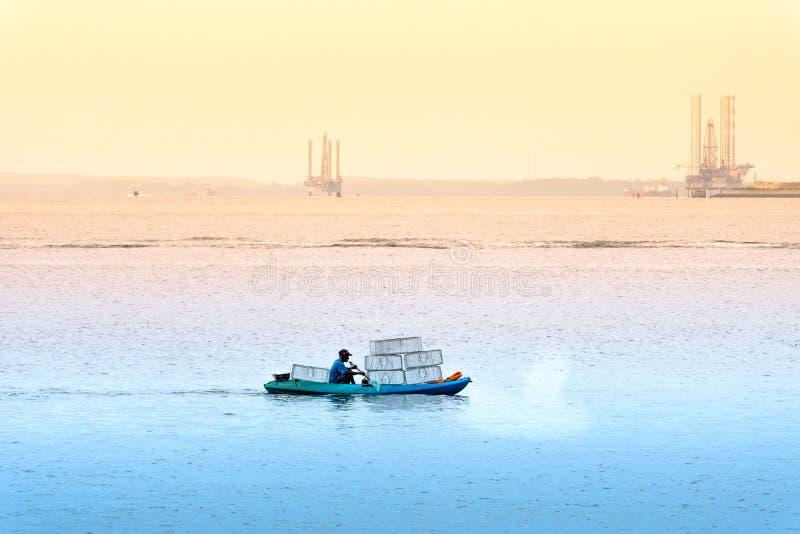 Singapur 29 DE JUNIO DE 2019: El pescador está pescando en el mar colocando jaulas foto de archivo