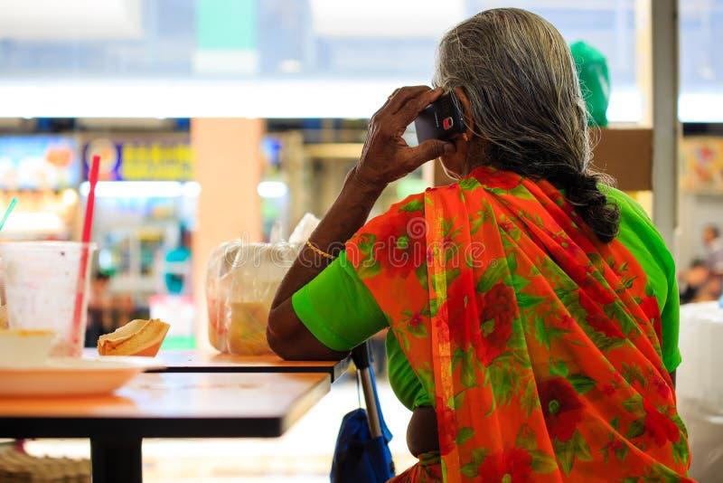 Singapur 11 DE MAYO DE 2019: teléfono indio de la mano del uso de la señora mayor en zona de restaurantes fotografía de archivo libre de regalías