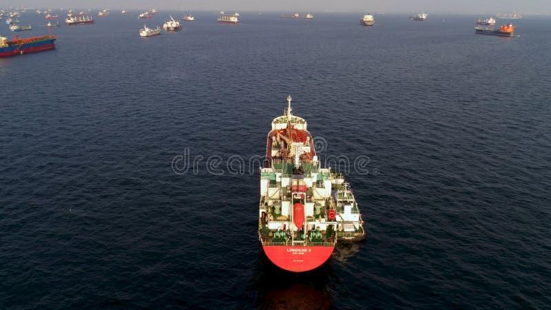 Singapur - 25 de septiembre de 2018: Vista aérea del buque rojo grande del envase o de carga en backgroung azul del mar y del cie foto de archivo