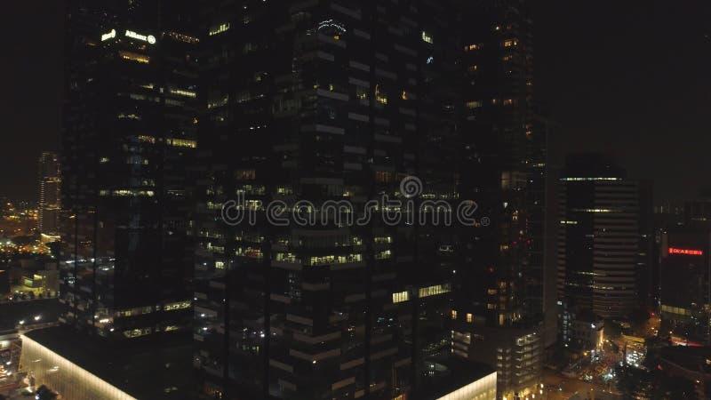 Singapur - 25 de septiembre de 2018: Windows con la gente que trabaja dentro de un edificio de oficinas en la noche en ciudad gra imagenes de archivo