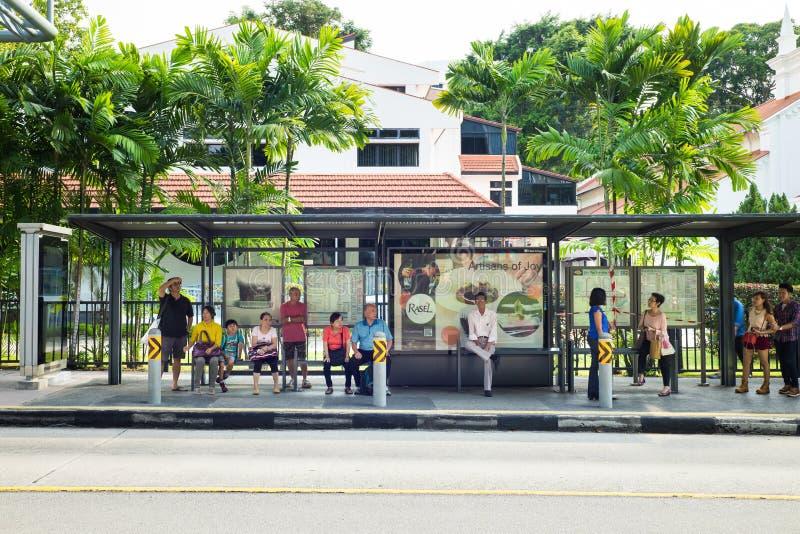 Singapur - 1. Mai 2016: Leutewartebus an der Bushaltestelle im Obstgarten Rd, Singapur lizenzfreies stockbild