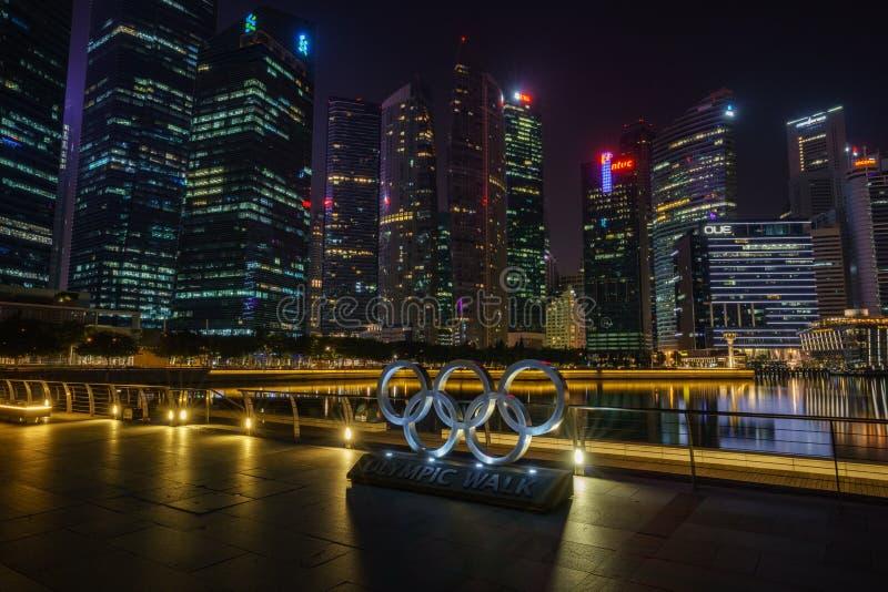 Singapur, Październik - 16, 2018: olimpijscy pierścionki przed drapacz chmur pieniężny okręg przy nocą, marina zatoka fotografia stock