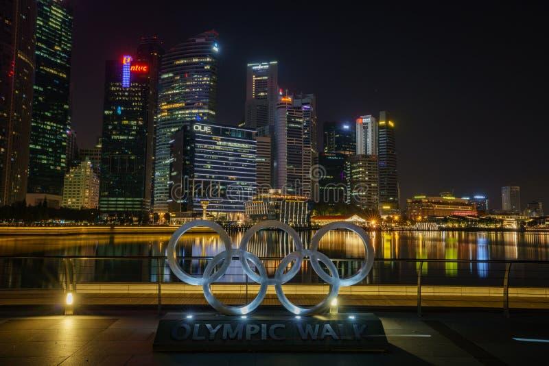 Singapur, Październik - 16, 2018: olimpijscy pierścionki przed drapacz chmur pieniężny okręg przy nocą, marina zatoka obrazy royalty free