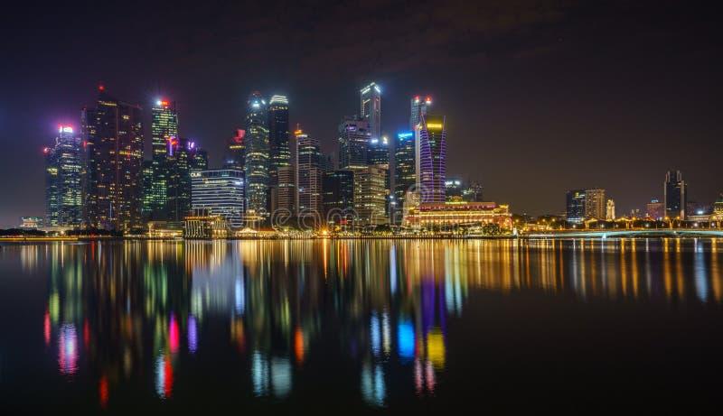 Singapur, Październik - 15, 2018: Panorama drapacz chmur, merlion i most przy marina, trzymać na dystans przy nocą fotografia royalty free