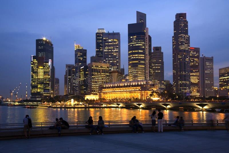 Singapur-Skyline und Leute an der Dämmerung lizenzfreie stockfotografie