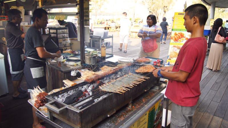 SINGAPURA - 3 de abril de 2015: Os espetos saborosos deliciosos da galinha cozinham sobre carvões quentes no alimento da rua do ` imagens de stock