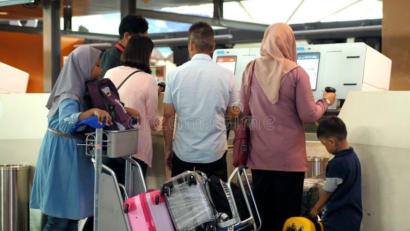 Singapura, o 13 de julho de 2018 Bagagem grande asiática do registro da família em um transporte no aeroporto fotografia de stock