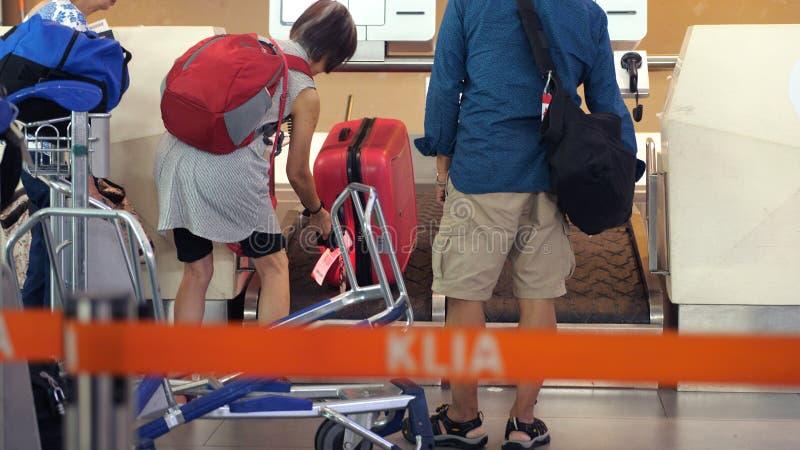 Singapura, o 13 de julho de 2018 Os viajantes registram a bagagem em um transporte no aeroporto fotos de stock