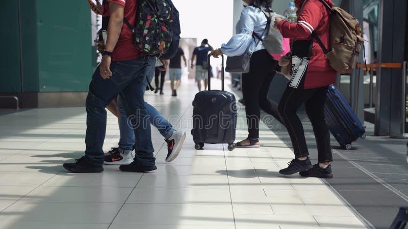 Singapura, o 13 de julho de 2018, povos irreconhecíveis com bagagens que andam no aeroporto terminal Feche acima dos pés foto de stock royalty free