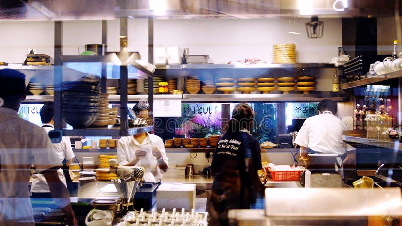 Singapura, o 26 de maio de 2018 A cozinha no restaurante, os trabalhadores ajustou a ordem, limpado, lavada, desmonta contas fotografia de stock
