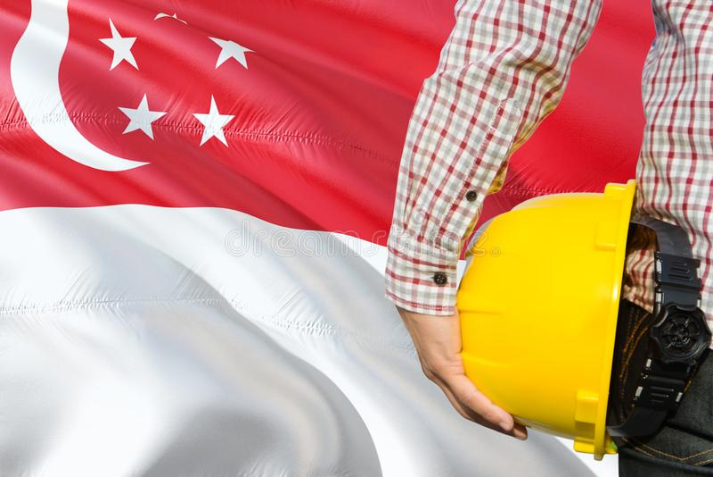 Singapurski inżynier trzyma żółtego zbawczego hełm z machać Singapur chorągwianego tło Budowy i budynku poj?cie zdjęcia royalty free