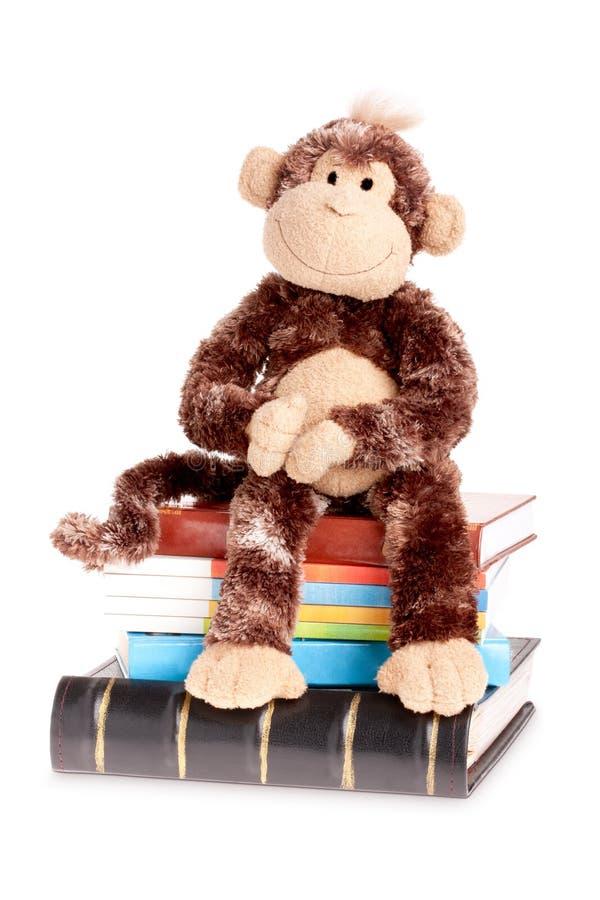 Singe mou de chéri de jouet sur la pile des livres photos stock