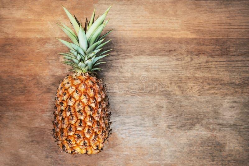 Singel en mycket hel organisk ananasfrukt på moget fullvuxet moget för träbakgrund, lagt ner på dess sida negativt tomt s arkivfoto