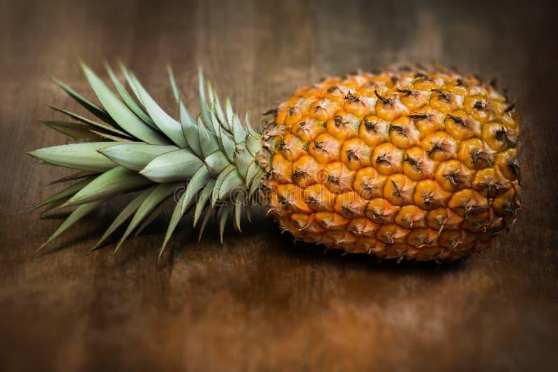 Singel en mycket hel organisk ananasfrukt på moget fullvuxet moget för träbakgrund, lagt ner på sidan fotografering för bildbyråer