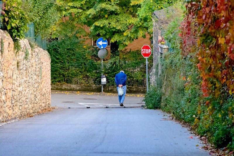 Singel krökt gamal man som går ner gatan Sociala problem av gamlingen, armod arkivbild
