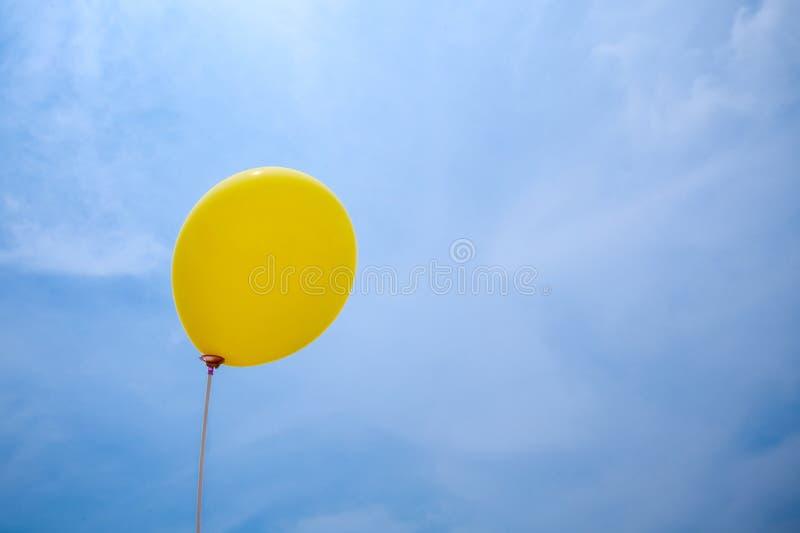 Singelgulingballong under molnig himmel handen rymmer ballongrepet upp till himlen royaltyfria bilder