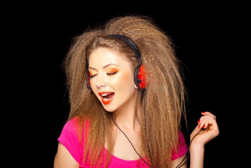 Singendes Mädchen während hörende Musik auf Kopfhörern lizenzfreies stockfoto