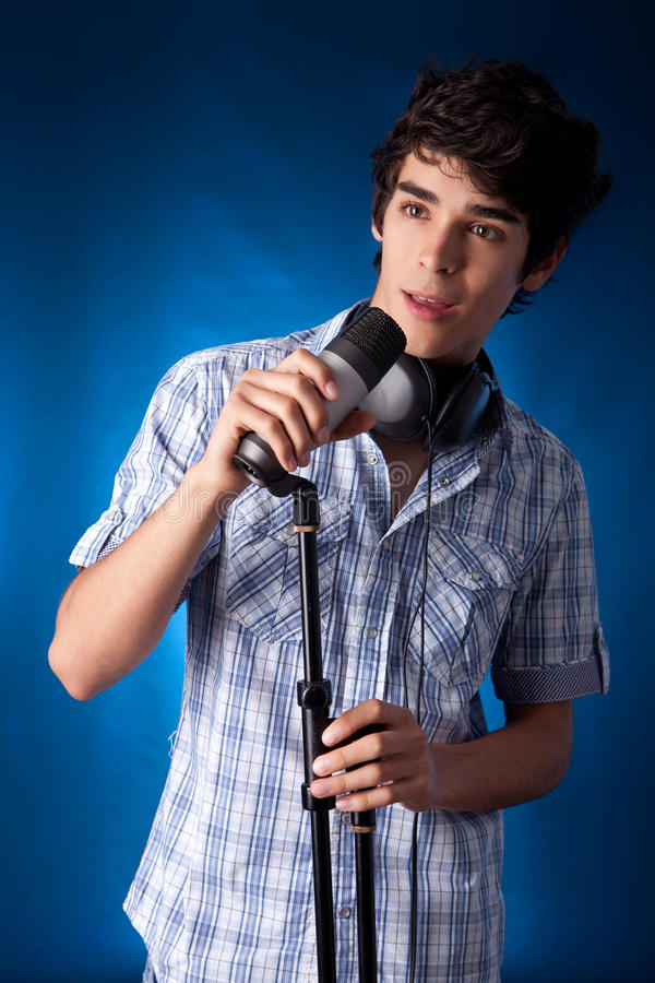 Singer. Young and very hansome boy singing, on blue background royalty free stock image