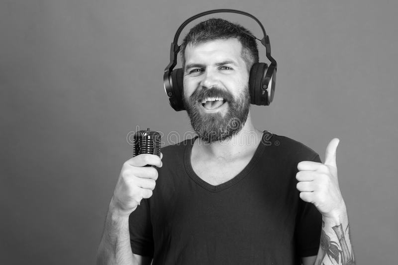 Singer with beard and smiling face listens to music. Pleasure, music and creative lifestyle concept. Dj with beard royalty free stock photography