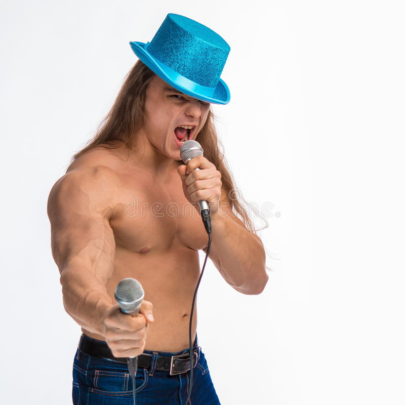 Singer bodybuilder shirtless with long hair in a blue hat with a microphone. On a white background stock photography