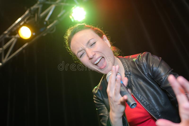 Singer hand holding microphone and singing stock photo