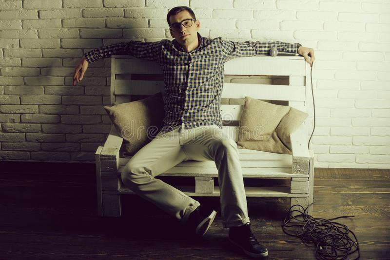 Man in glasses and checkered shirt on bench with microphone stock image