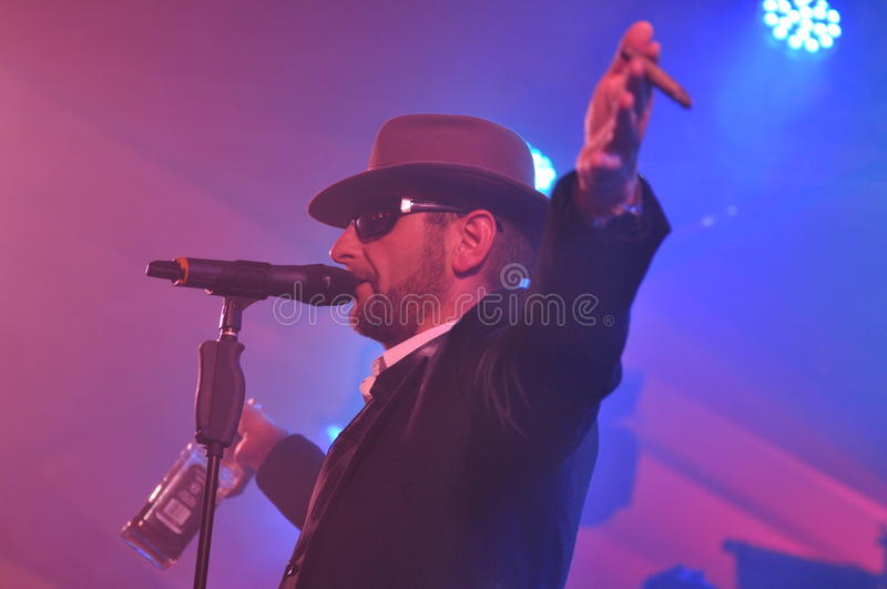 Singer with hat and cigar at microphone. Male singer onstage with hat, cigar, bottle of Whisky at microphone, band. alpenmafia (see: www.alpenmafia.de ) at royalty free stock image
