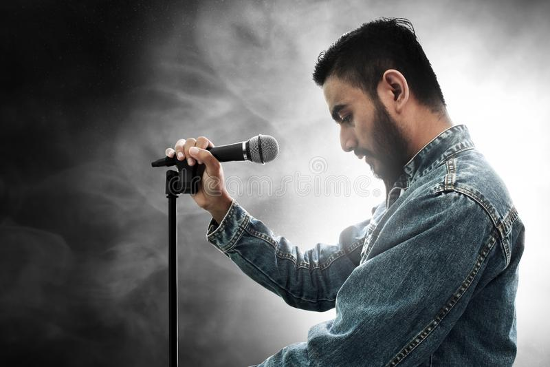 Singer holding microphone on smoke background. S royalty free stock photography