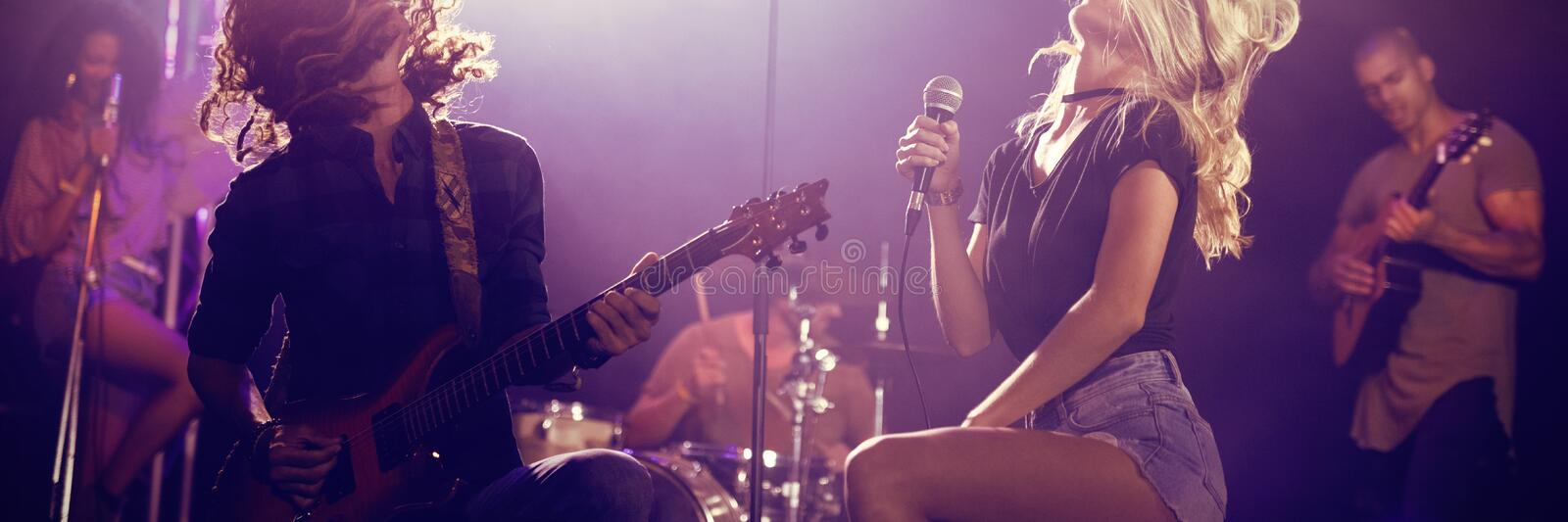 Singer and male guitarist with tousled hair performing at nightclub. Female singer and male guitarist with tousled hair performing together on stage at nightclub royalty free stock photos
