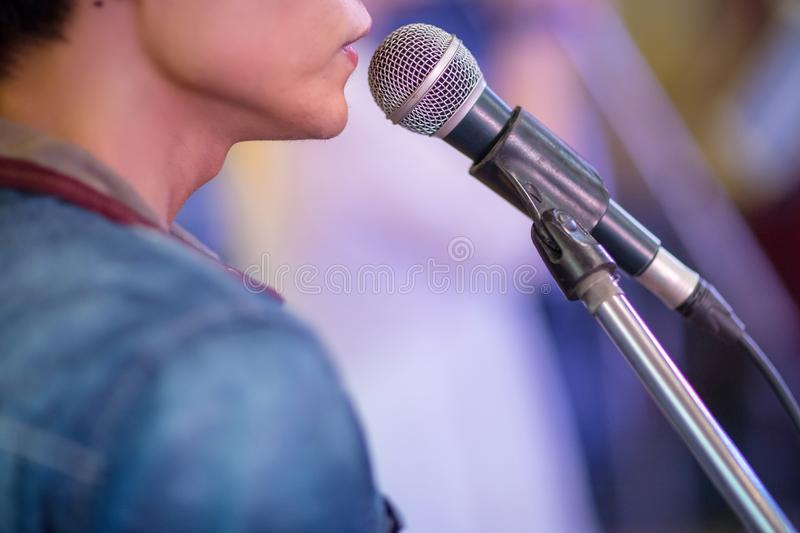 singer and microphone. Close up image of man singing to a microphone. royalty free stock photography