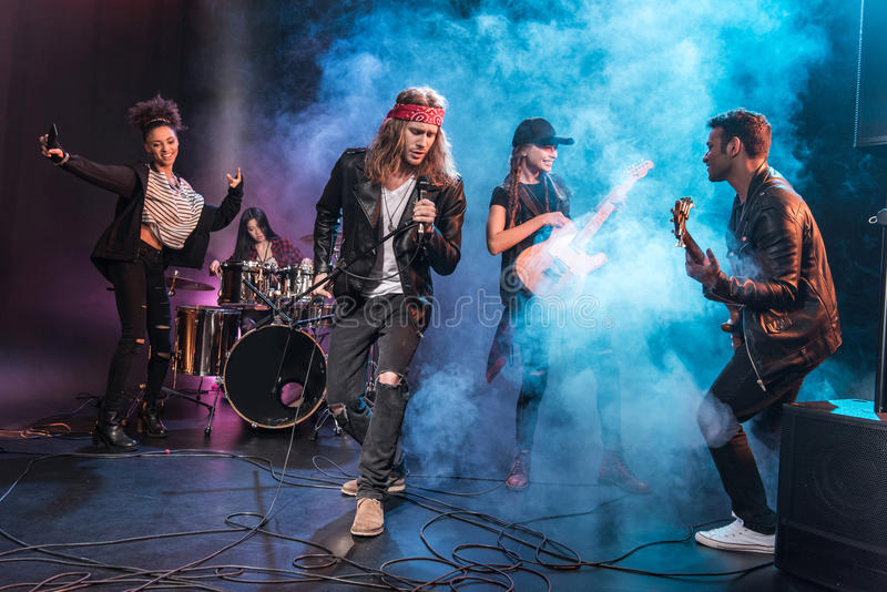 Singer with rock and roll band performing music on stage. Handsome singer with rock and roll band performing music on stage royalty free stock photo