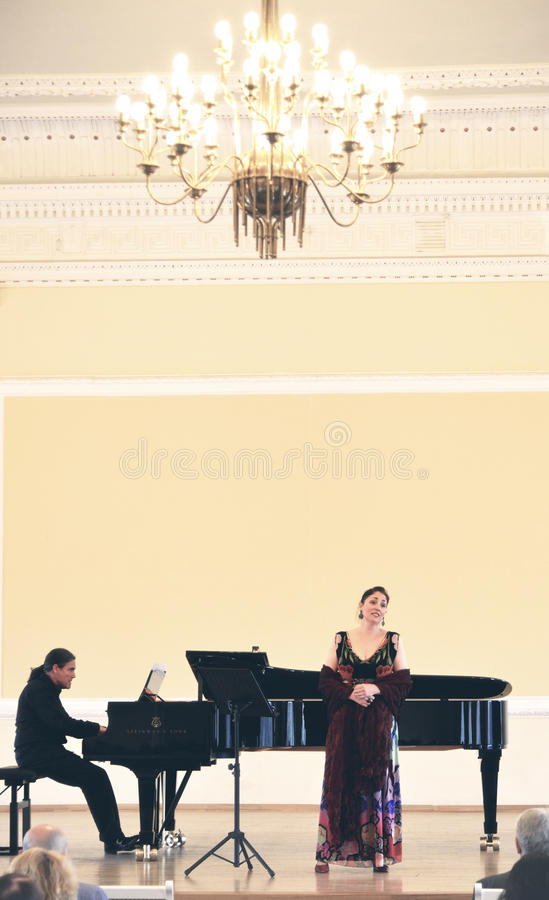 Singer sings in the concert at academy, lithuania. Woman sings at opera concert and a musician accompanies with piano stock photography