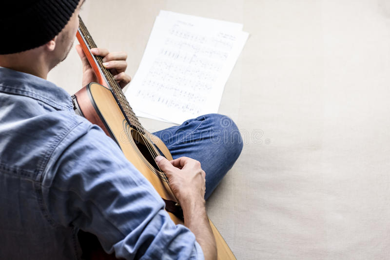 Singer songwriter plays song from sheet music tabs royalty free stock photo