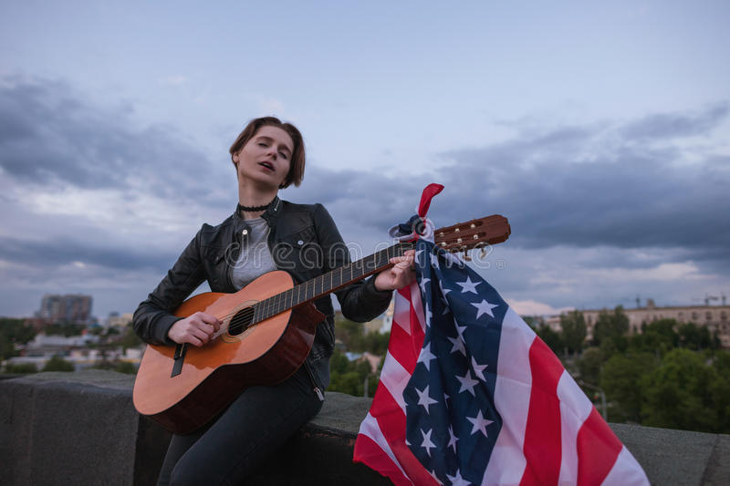 Singer with the US flag playing the guitar. On cloudy sky background. Acoustic concert on the roof. A teenager on vacation at a party on Independence Day stock photography